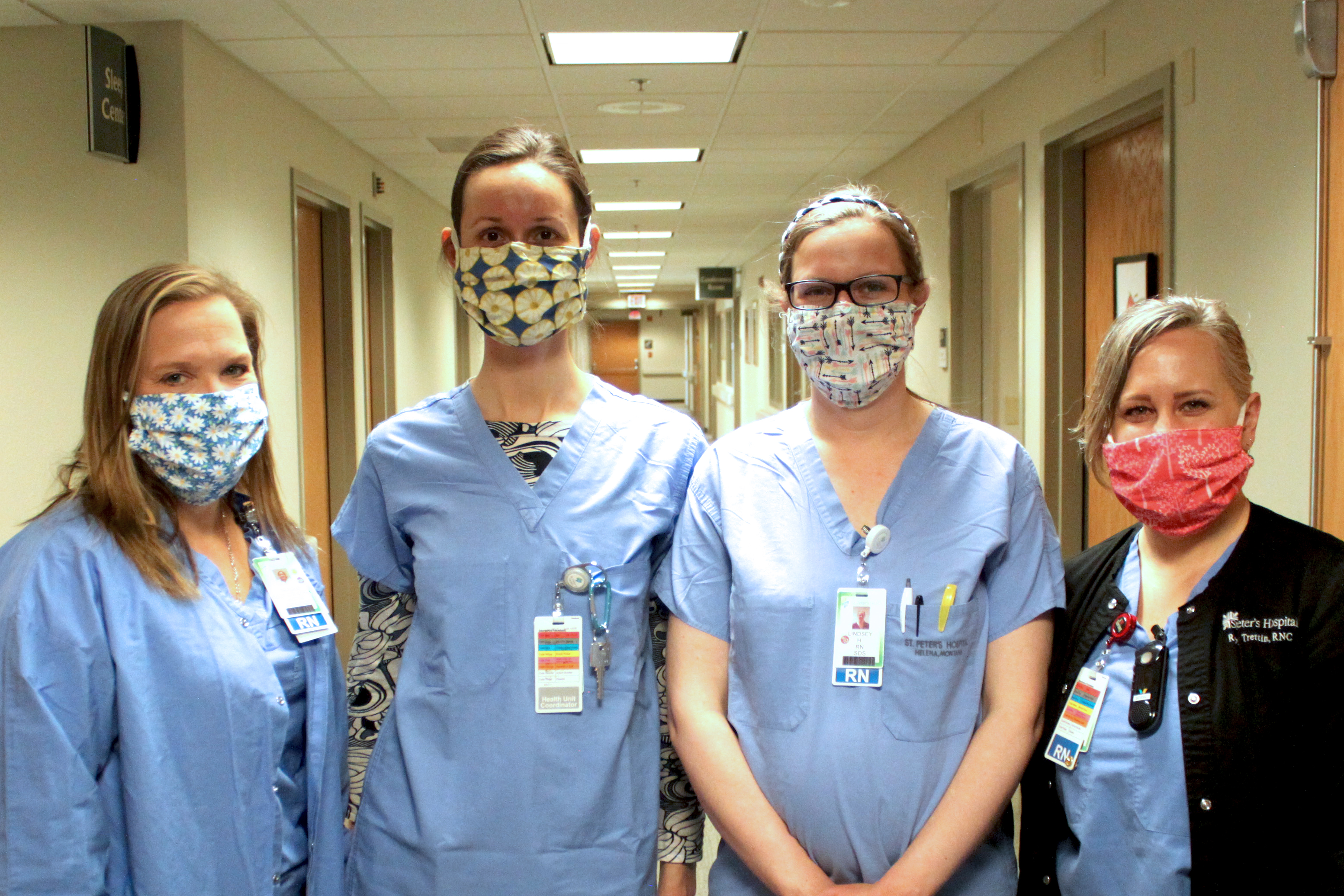 Caregivers pose wearing cloth masks donated by community members