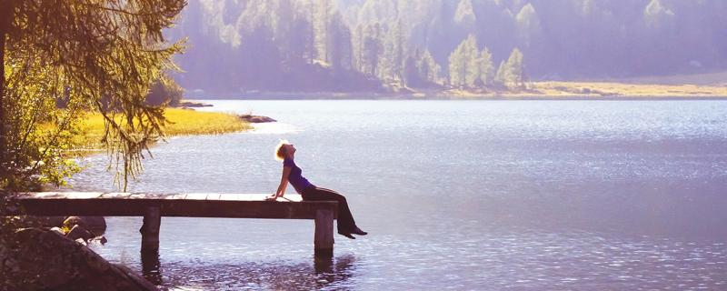 person sitting on a dock overlooking the water