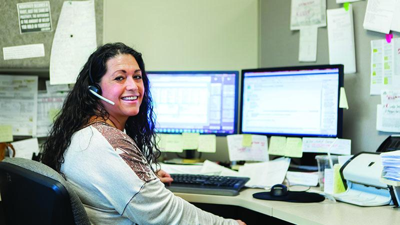 SPH Careers - Employee at desk smiling