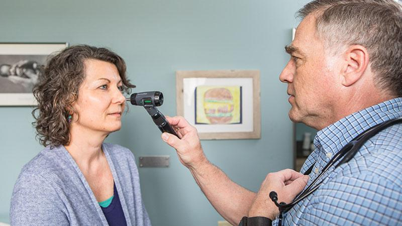 SPH family medicine provider checking patient's eyes